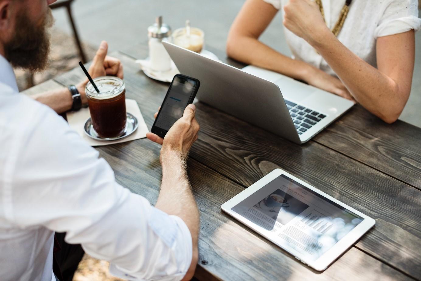 Zwei Personen sitzen mit Laptop und Smartphone am Tisch - Telefonkonferenzen an jedem Ort zu jeder Zeit