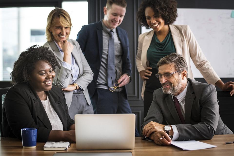 Menschen schauen gemeinsam auf Laptop - Telefonkonferenzen als Win-Win-Situation