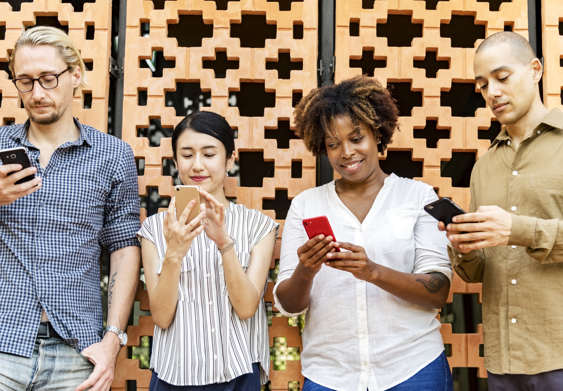 Menschen vor Wand mit Smartphones in der Hand
